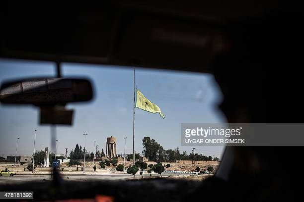 A Kurdish People's Protection Units flag is seen through a car window on June 22 in the northern Syrian town of Tal Abyad on the border with Turkey...