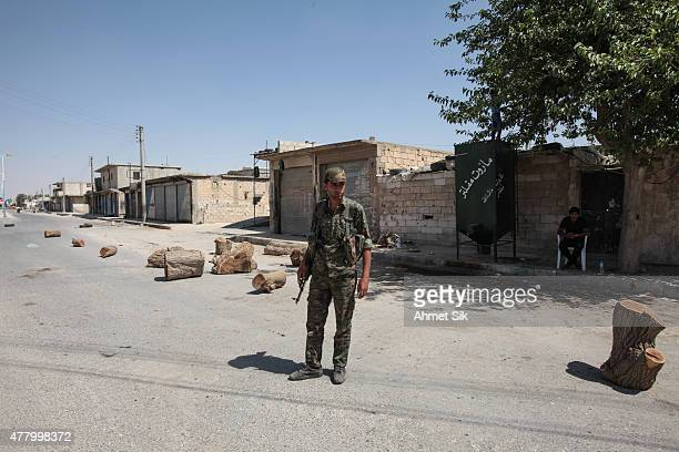 A Kurdish People's Protection Units or YPG fighter controls downtown of Tal Abyad Syria June 19 2015 Kurdish fighters with the YPG took full control...