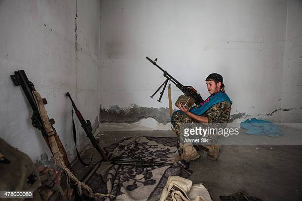 A Kurdish People's Protection Units or YPG fighter controls the weapons in downtown of Tal Abyad Syria June 19 2015 Kurdish fighters with the YPG...