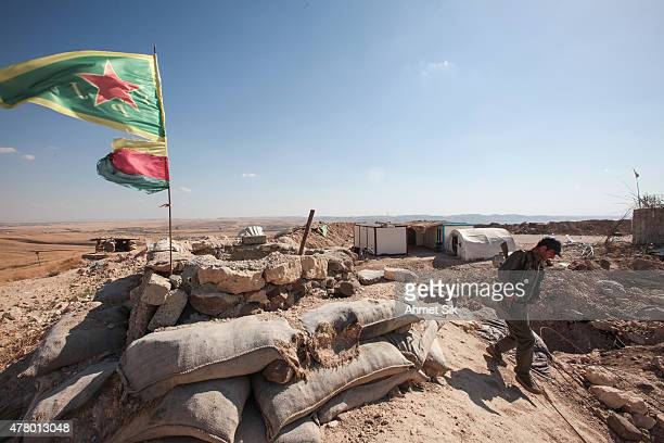 A Kurdish People's Protection Units or YPG fighter walks in a check point in the outskirts of the destroyed Syrian town of Kobane also known as Ain...