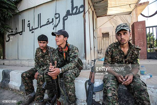 Kurdish People's Protection Units or YPG fighters rest in Tal Abyad Syria June 19 2015 Kurdish fighters with the YPG took full control of Tal Abyad...