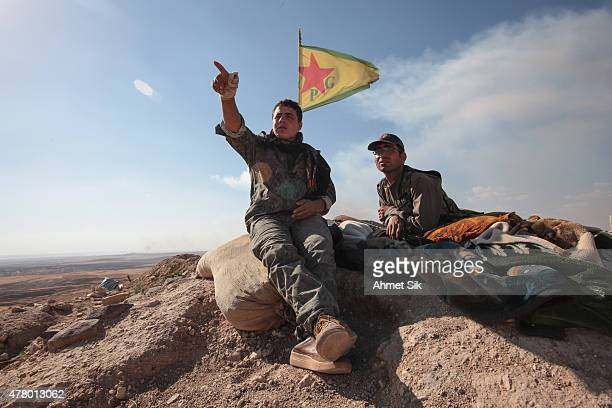 A Kurdish People's Protection Units or YPG fighters sit near a check point in the outskirts of the destroyed Syrian town of Kobane also known as Ain...