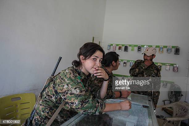 Kurdish People's Protection Units or YPG woman fighters rests in Tal Abyad Syria June 19 2015 Kurdish fighters with the YPG took full control of Tal...