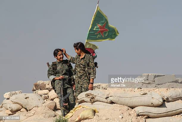 A Kurdish People's Protection Units or YPG women fighters chat as they stand near a check point in the outskirts of the destroyed Syrian town of...