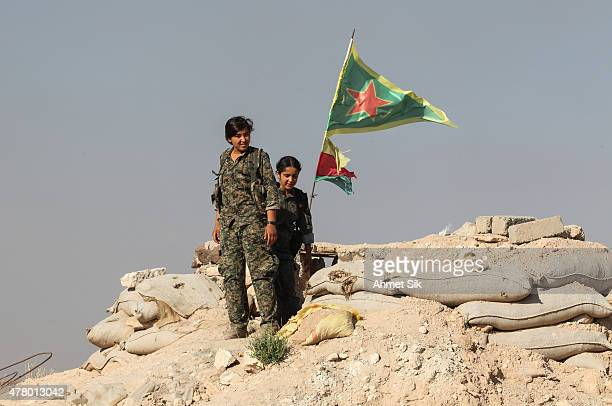A Kurdish People's Protection Units or YPG women fighters pose as they stand near a check point in the outskirts of the destroyed Syrian town of...