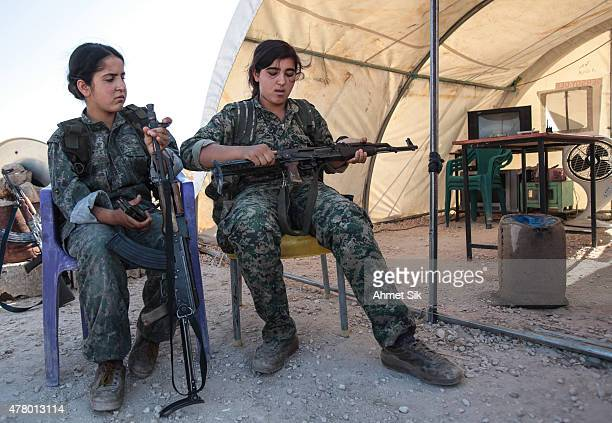 A Kurdish People's Protection Units or YPG's woman fighter controls her AK47 in a camp at the outskirts of the destroyed Syrian town of Kobane also...