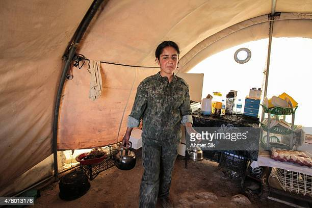 A Kurdish People's Protection Units or YPG's woman fighter cooks in a base camp at the outskirts of the destroyed Syrian town of Kobane also known as...