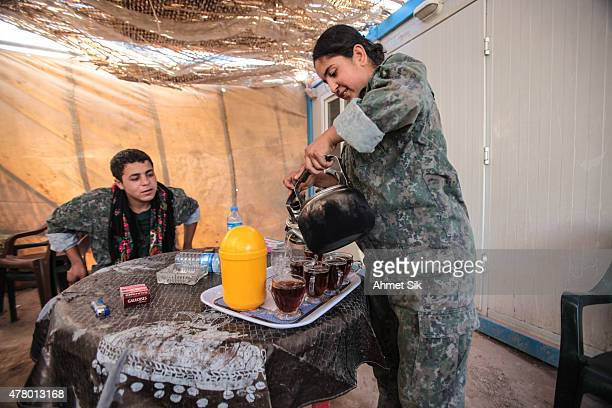A Kurdish People's Protection Units or YPG's woman fighter pours tee in a base camp at the outskirts of the destroyed Syrian town of Kobane also...