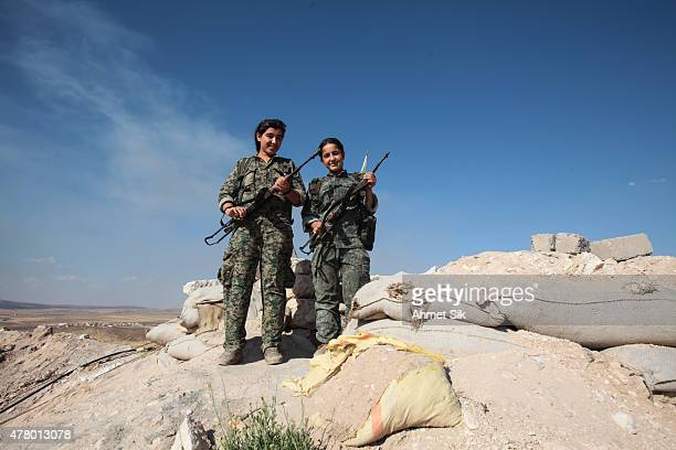 Kurdish People's Protection Units or YPG's women fighters pose as they stand in a check point with their AK47 at the outskirts of the destroyed...