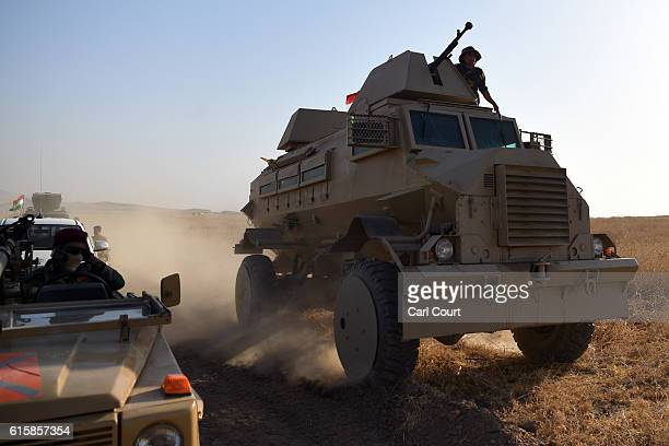 Kurdish peshmerga armoured vehicles move forward during an assault to recapture the village of Tiskharab from ISIS on October 20 2016 near Mosul Iraq...