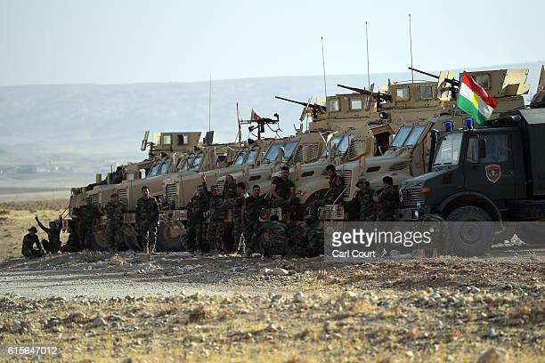 Kurdish peshmerga engineers stand next to their armoured vehicles near a road to Mosul as forces continue the battle to retake Mosul on October 19...