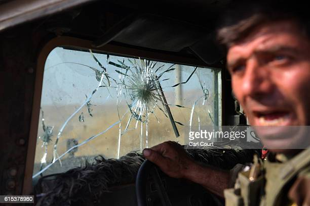 Kurdish Peshmerga fighter leans out of his military vehicle which has taken several direct hits from ISIS snipers including on the windscreen on...