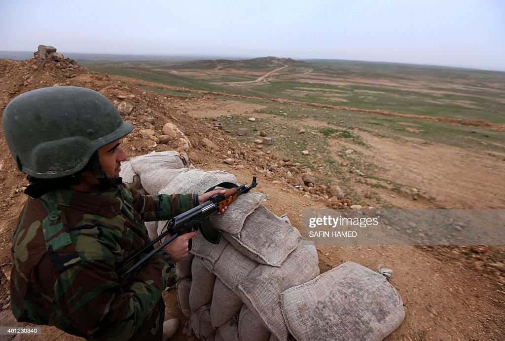 A Kurdish Peshmerga fighter stands guard at a position on the frontline in the Gwer district 40 kilometres south of Arbil the capital of the Kurdish...