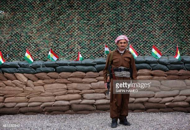 A Kurdish Peshmerga fighter stands in front of a line of Kurdish flags at a position on the frontline in the Gwer district 40 kilometres south of...