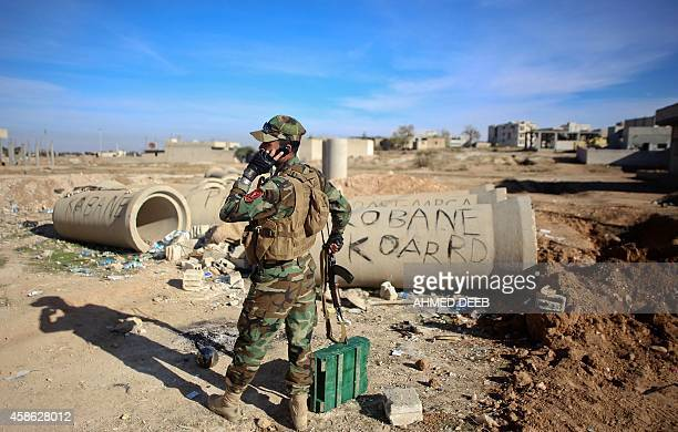 A Kurdish Peshmerga fighter talks on the phone during fighting against Islamic State group on November 8 2014 in the Syrian besieged border town of...