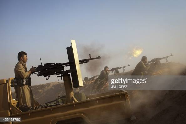 Kurdish Peshmerga fighters fire a Duskha heavy machine gun as they hold a position on the front line in the Gwer district 40 kilometres south of...