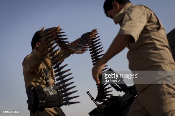 Kurdish Peshmerga fighters load a Duskha heavy machine gun as they hold a position on the front line in the Gwer district 40 kilometres south of...
