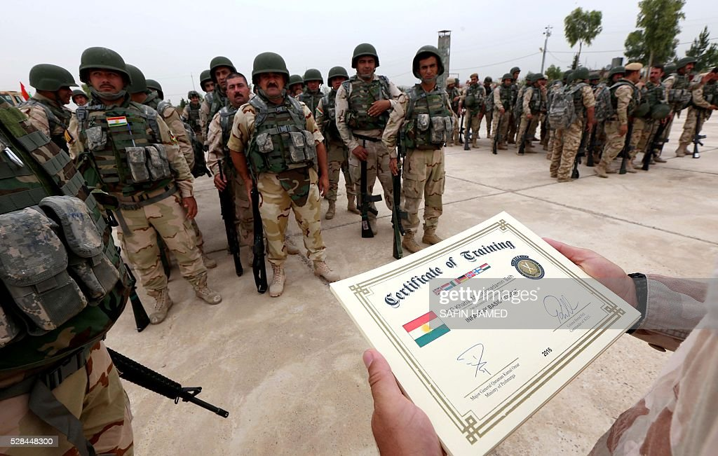 Kurdish Peshmerga fighters receive a certificate of training during a graduation ceremony on May 5, 2016 at the Kurdistan Training Coordination Center (KTTC) of Arbil, the capital of the autonomous Kurdish region of northern Iraq. The KTTC is a joint effort of the Dutch, Italian, British and German governments which aims to unify the military assistance of these countries. / AFP / SAFIN
