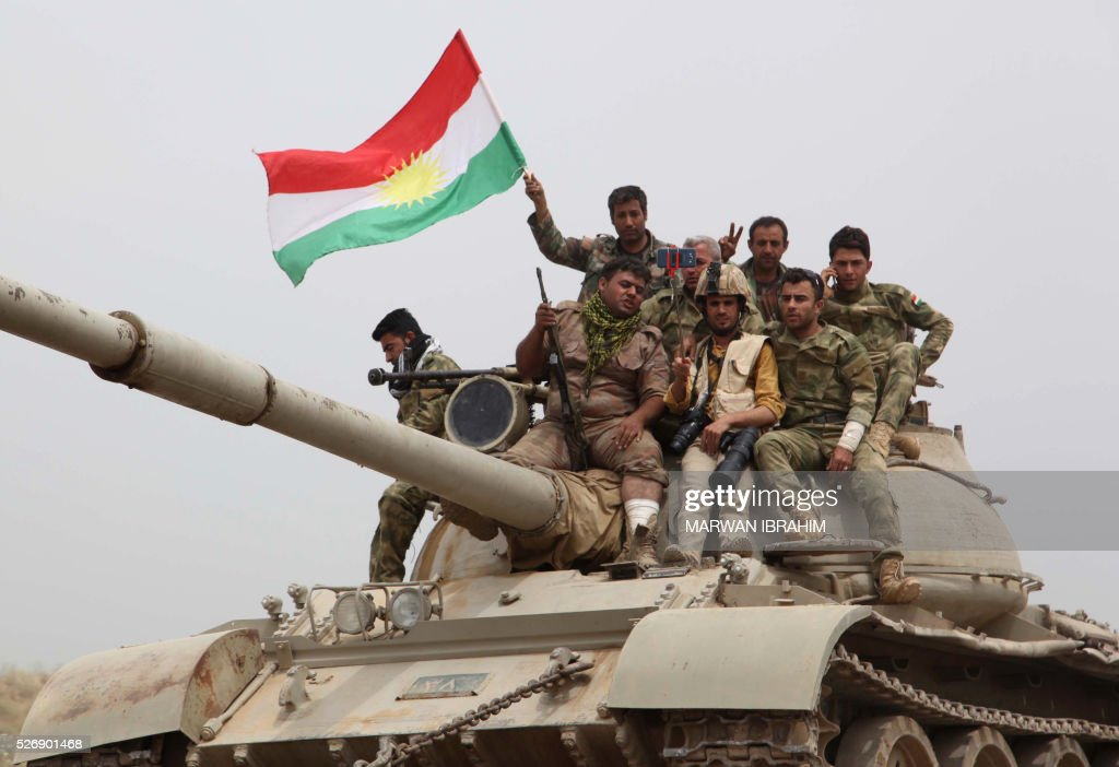 Kurdish Peshmerga fighters sit on top of a tank waving the Kurdish flag on the front line some 35 kilometres south of Kirkuk after they recaptured the northern Iraqi town of Bashir from the Islamic State (IS) group on May 1, 2016. / AFP / Marwan IBRAHIM