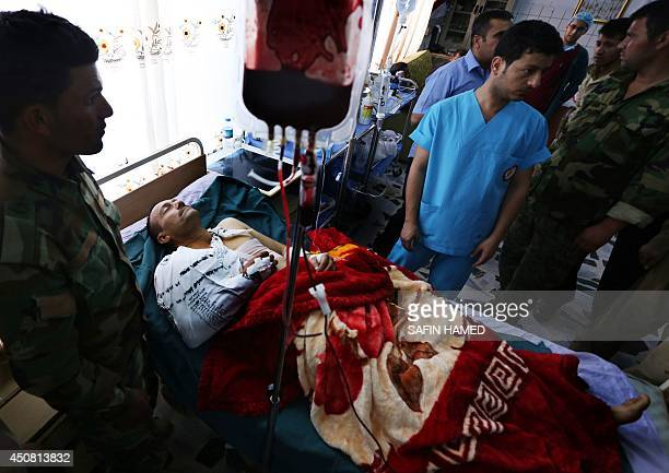 Kurdish Peshmerga fighters stand next to the bed of a comrade wounded in clashes with jihadists from the Islamic State of Iraq and the Levant in...