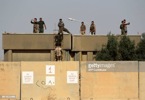 Kurdish peshmerga fighters stand on the roof top of a building as they hold a position on the opposition side of river bank from Iraqi forces on the...