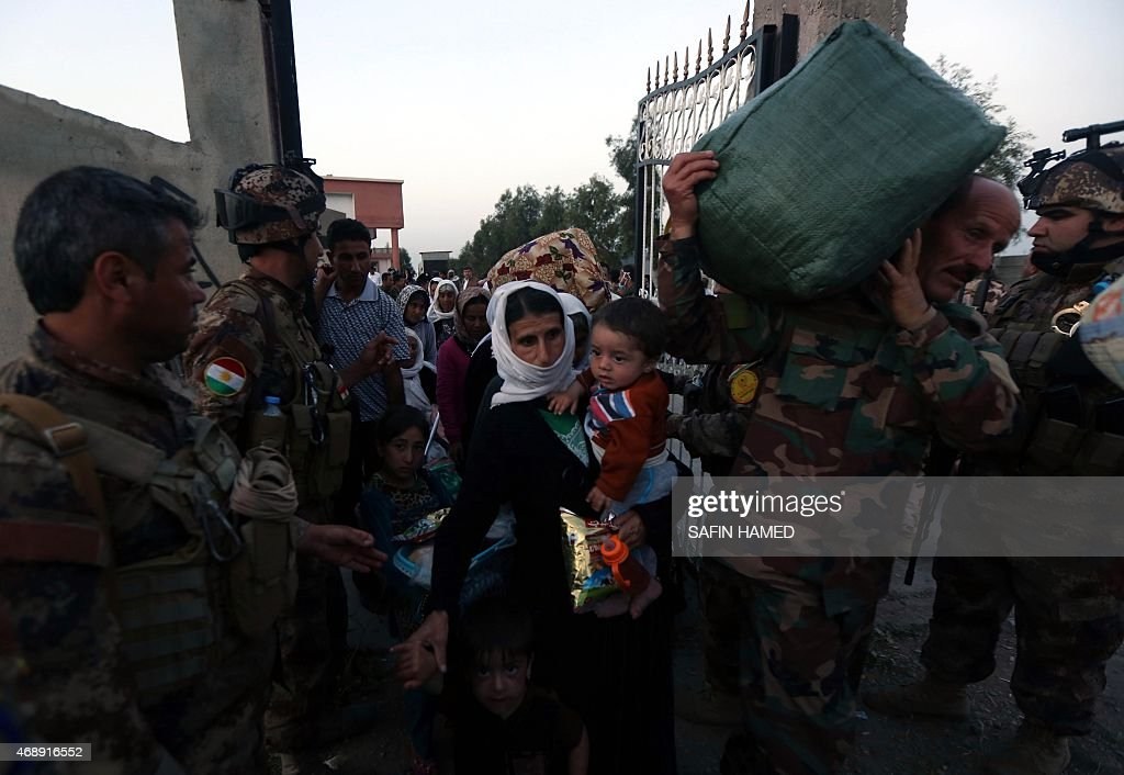 Kurdish Peshmerga forces help people from Iraq's Yazidi minority as they arrive at a medical center in the town of Altun Kupri some 20 kms northeast...