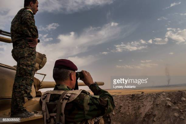 Kurdish Peshmerga forces look out at smoke rising from American air strikes in the village of Resala as they stand in overwatch positions near the...