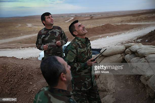 Kurdish Peshmerga forces look towards a US military war plane flying over the frontline with ISIS November 5 2015 near Telskuf in northern Iraq All...