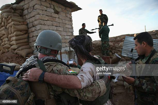 Kurdish Peshmerga forces pose for photos with a former US Marine volunteer on November 5 2015 on the frontline against ISIS fighters in Telskuf...