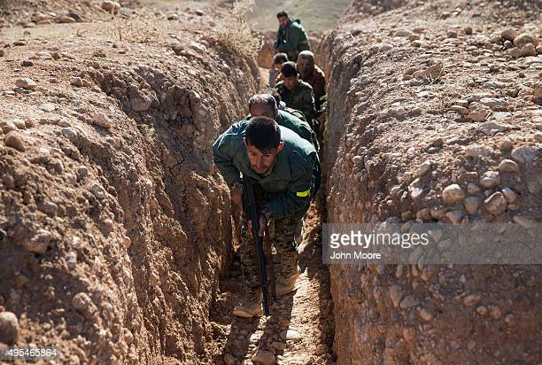 Kurdish Peshmerga forces run through a trench during the last week of a military training course on November 3 2015 in Erbil Iraq The Kurdish troops...