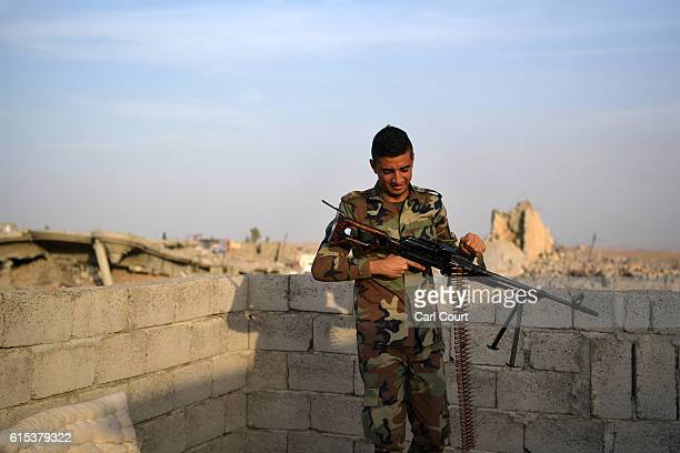 Kurdish Peshmerga holds a machine gun on the roof of a house in a village recently recaptured from ISIS on October 18 2016 in Bartella near Mosul...