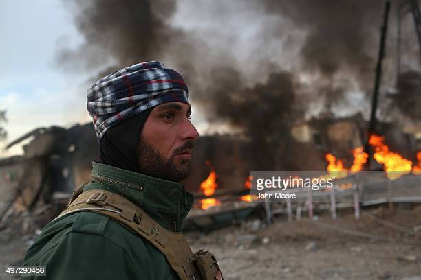 Kurdish Peshmerga soldier passes by tires set afire days before by ISIL extremists to hinder airstrikes on November 15 2015 in Sinjar Iraq Kurdish...
