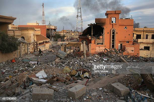 Kurdish Peshmerga soldier passes through the rubble of a neighborhood on November 15 2015 in Sinjar Iraq Kurdish forces with the aid of months of...