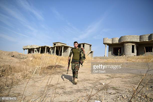 Kurdish Peshmerga soldier walks through a village recently recaptured from ISIS during the battle to retake Mosul on October 18 2016 in Bartella near...