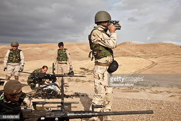 Kurdish peshmerga soldiers clean up shell casings after a training with the British military while another solider looks down the range with a scope...