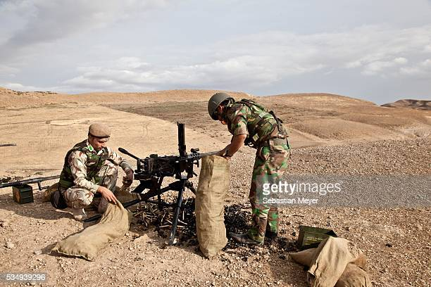 Kurdish peshmerga soldiers clean up shell casings after a training with the British military The British government has equipped the Kurdish...