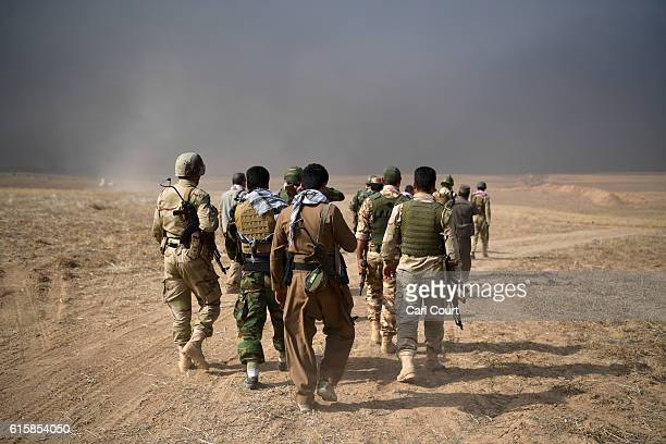 Kurdish peshmerga soldiers walk towards a position as smoke billows during an attack to recapture the village of Tiskharab on October 20 2016 near...