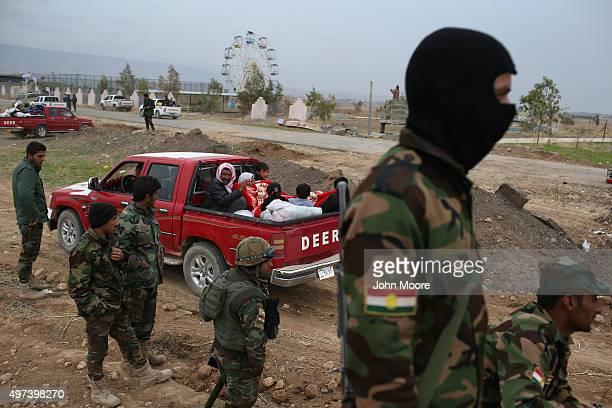 Kurdish Peshmerga soldiers watch as people flee an ISIL or in Arabic Daeshheld frontline village on November 16 2015 to Sinjar Iraq Peshmerga forces...