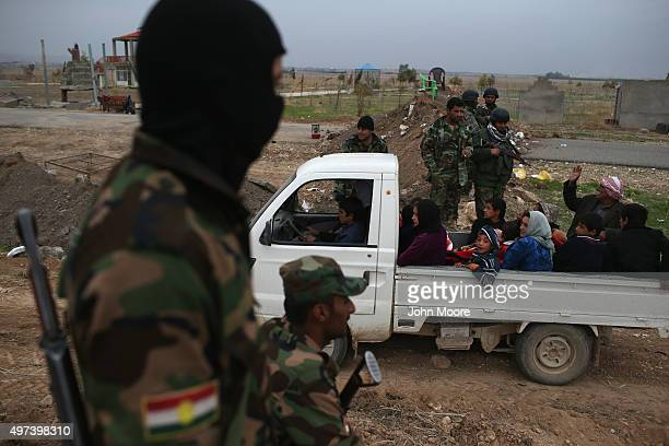 Kurdish Peshmerga soldiers watch as people flee an ISIL or in Arabic Daeshheld frontline village on November 16 2015 to Sinjar Iraq Peshmerga forces...