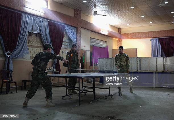 Kurdish Peshmerga troops play table tennis in a wedding hall now used as a military hospital on November 4 2015 near the frontline with ISIS fighters...