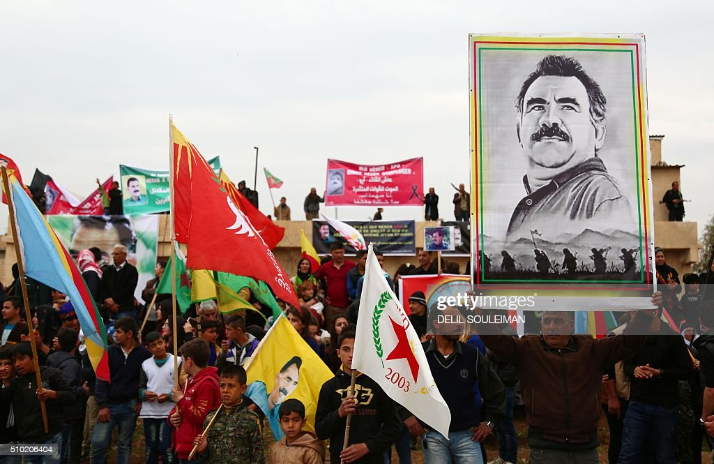 Kurdish protesters hold a portrait of Kurdistan Worker's Party (PKK) jailed leader Abdullah Ocalan on February 14, 2016, during a rally in the northeastern Syrian city of Qamishli to mark the 17th anniversary of his arrest by Turkish agents. / AFP / DELIL SOULEIMAN