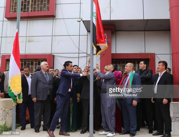 Kurdish provincial councillors watch on as the Iraqi and Kurdish flags are raised over a government building in the northern Iraqi city of Kirkuk on...