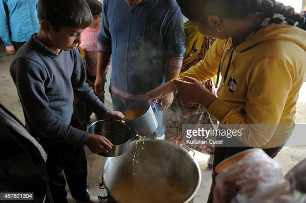 A Kurdish refugee boy from the Syrian town of Kobani holds a bowl for morning soup in a camp in the southeastern town of Suruc Sanliurfa province on...