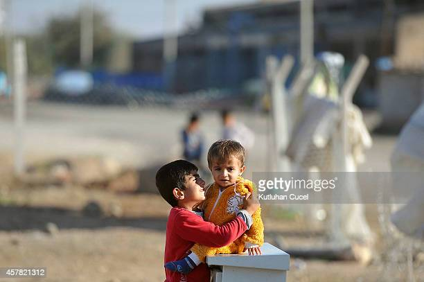 Kurdish refugee boy from the Syrian town of Kobani hugs his brother in a camp in the southeastern town of Suruc Sanliurfa province on October 25 2014...