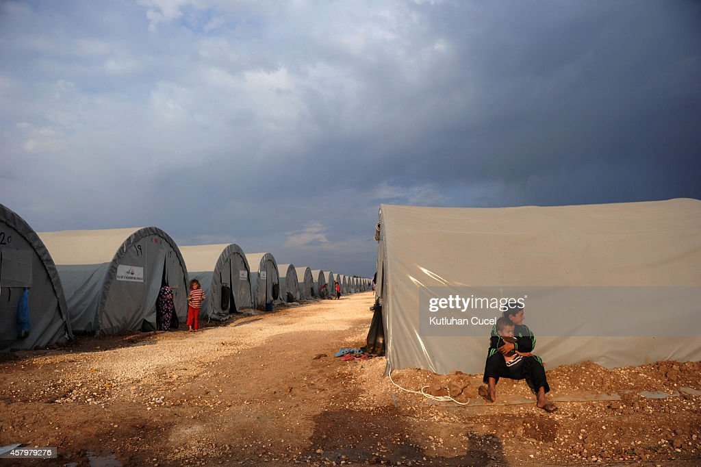 Kurdish refugee boys from the Syrian town of Kobani sit near their family tent in a camp in the southeastern town of Suruc Sanliurfa province October...