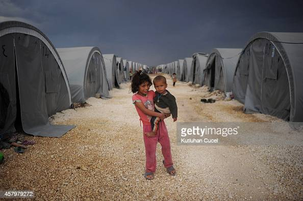 Kurdish refugee children from the Syrian town of Kobani look on near makeshift tents in a camp in the southeastern town of Suruc Sanliurfa province...