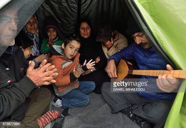 A Kurdish refugee family plays traditional music inside their tent at a makeshift camp at the GreekMacedonian border near the Greek village of...