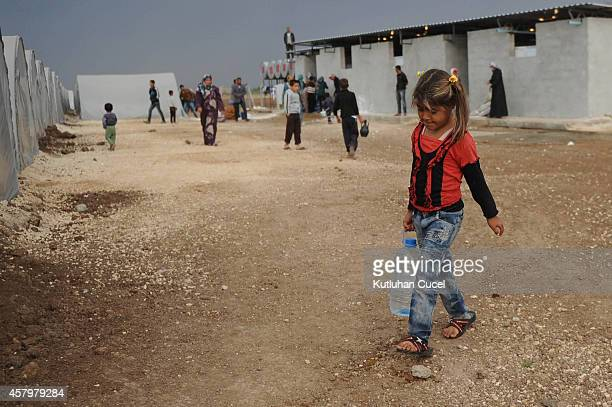 A Kurdish refugee girl from the Syrian town of Kobani carries water in a camp in the southeastern town of Suruc Sanliurfa province October 28 2014...
