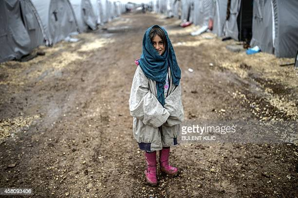 A Kurdish refugee girl stands during a rainy day at the Rojova Camp in Suruc a rural district of Sanliurfa Province on October 30 2014 Heavily armed...