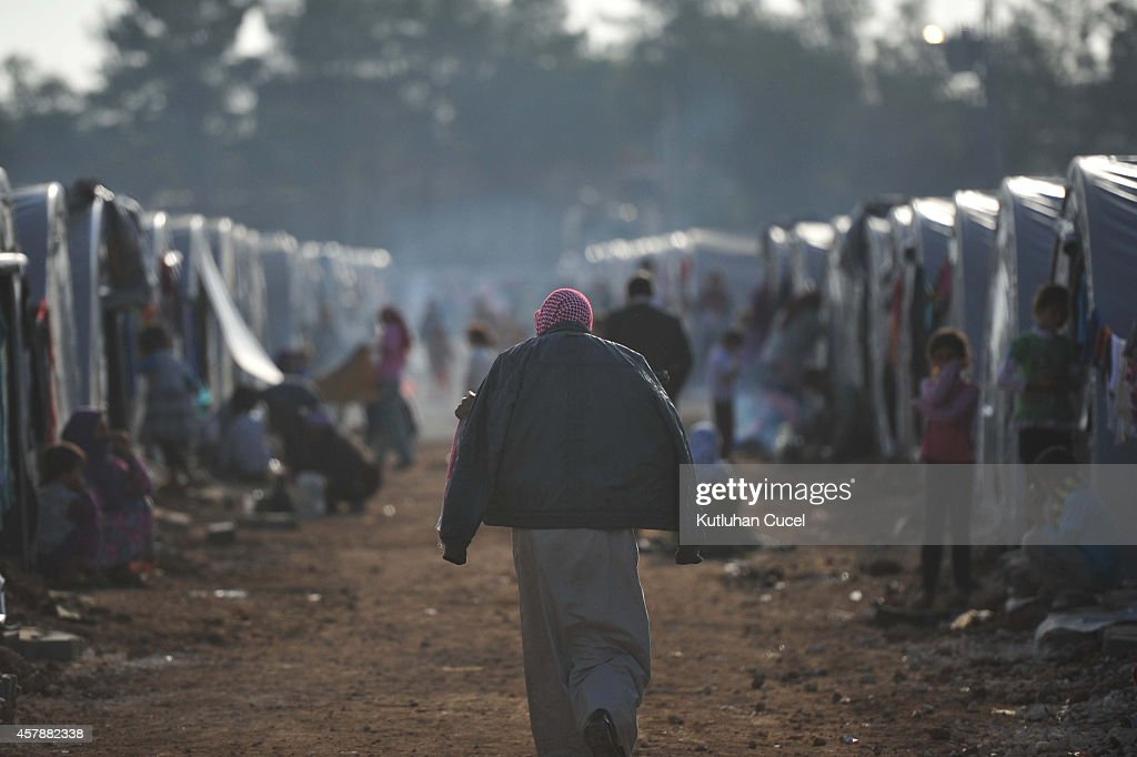 A Kurdish refugee man walks past the tents in a refugee camp on October 26 2014 in the southeastern town of Suruc Turkey The Syrian town of Kobani...